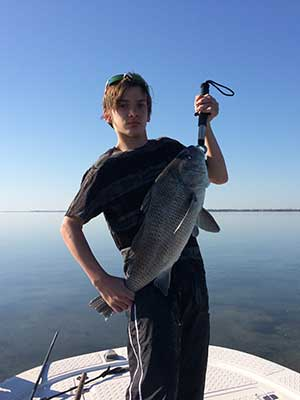 Young man with Black Drum caught in Mosquito Lagoon