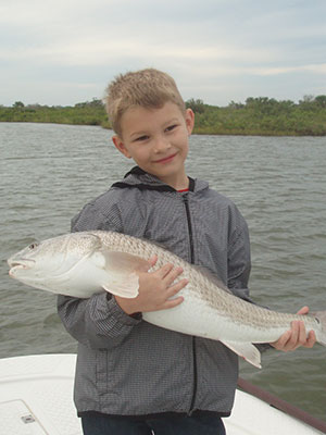Cute kid with Redfish caught near New Smyrna Beach